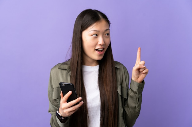 Jong chinees meisje die mobiele telefoon over geïsoleerde purper met behulp van van plan zijn om de oplossing te realiseren terwijl het opheffen van een vinger