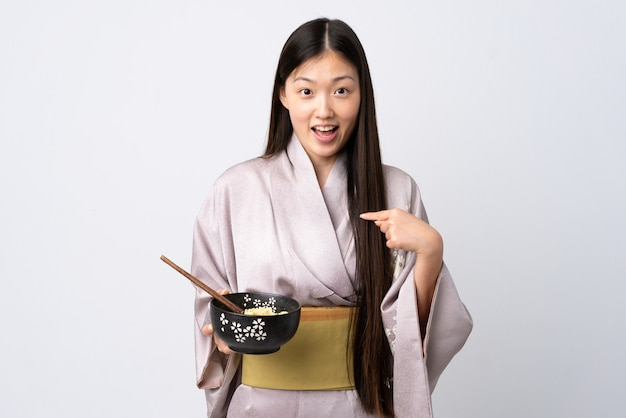Jong chinees meisje draagt kimono over geïsoleerde witte achtergrond met verrassende gezichtsuitdrukking terwijl ze een kom noedels met eetstokjes vasthoudt