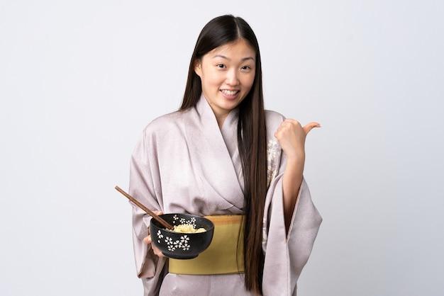Jong chinees meisje draagt kimono over geïsoleerde witte muur wijzend naar de zijkant om een product te presenteren terwijl ze een kom noedels met stokjes vasthoudt