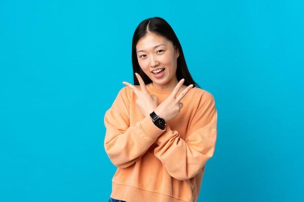 Jong chinees meisje geïsoleerd glimlachend en overwinningsteken tonen