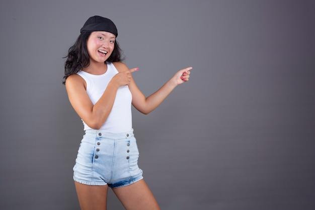Jong chinees meisje met bandana en geïsoleerd t-shirt wijzend naar de zijkant die iets laat zien.