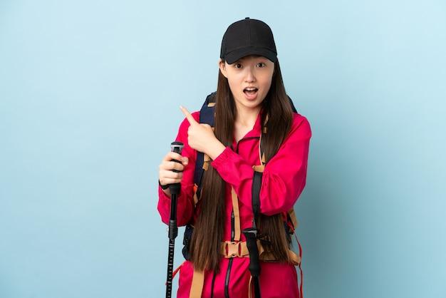 Jong chinees meisje met geïsoleerde rugzak en trekkingsstokken
