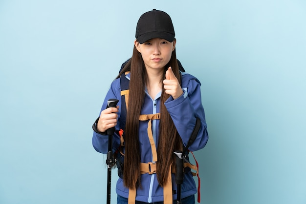 Jong chinees meisje met rugzak en trekking stokken over geïsoleerde blauwe muur gefrustreerd en wijzend naar de voorkant