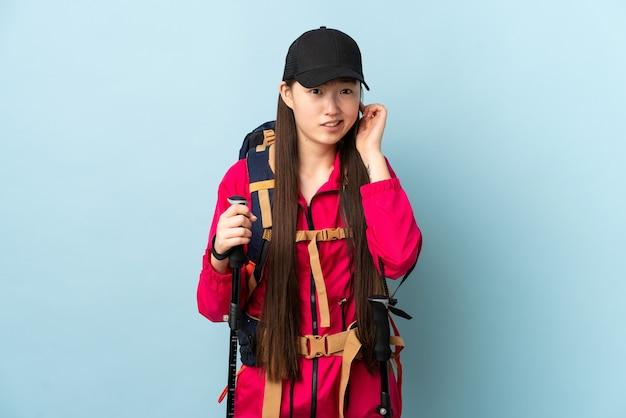 Jong chinees meisje met rugzak en trekkingsstokken over geïsoleerde blauwe gefrustreerde muur en behandelende oren