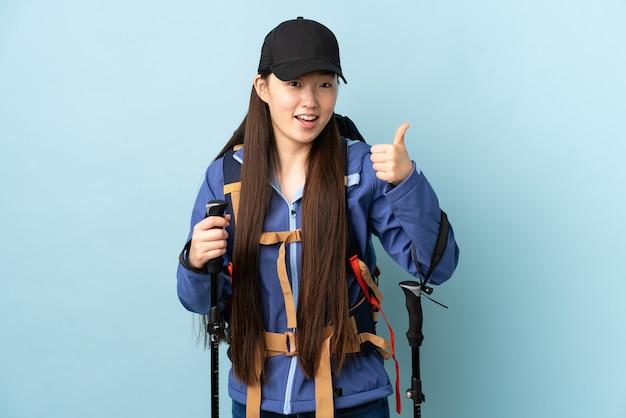 Jong chinees meisje met rugzak en trekkingsstokken over geïsoleerde blauwe muur die duimen op gebaar geven