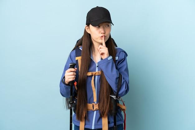 Jong chinees meisje met rugzak en trekkingsstokken over geïsoleerde blauwe muur die een teken van stiltegebaar tonen die vinger in mond zetten