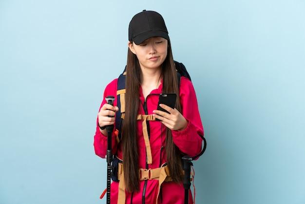Jong chinees meisje met rugzak en trekkingsstokken over geïsoleerde blauwe muur die en een bericht denken verzenden