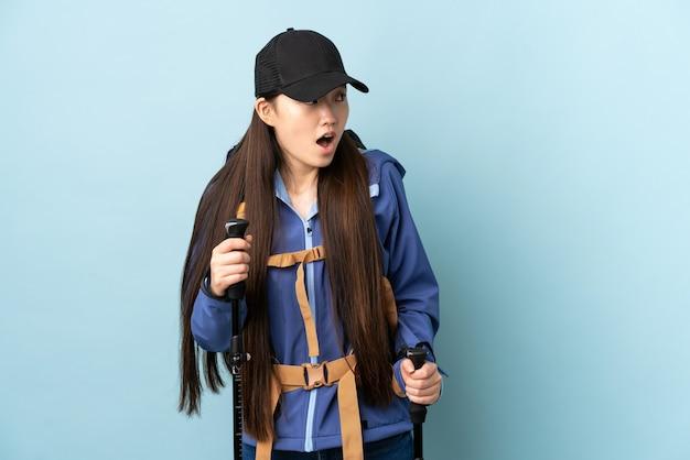Jong chinees meisje met rugzak en trekkingsstokken over geïsoleerde blauwe muur die verrassingsgebaar doen terwijl het kijken naar de kant