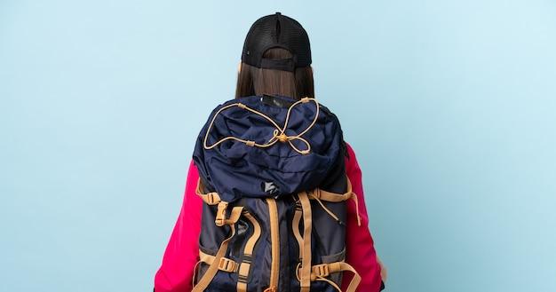 Jong chinees meisje met rugzak en trekkingsstokken over geïsoleerde blauwe muur in achterpositie