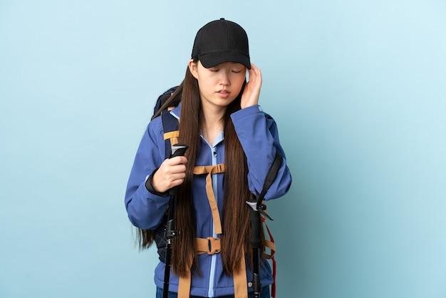 Jong chinees meisje met rugzak en trekkingsstokken over geïsoleerde blauwe muur met hoofdpijn