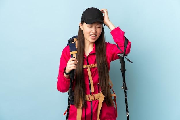 Jong chinees meisje met rugzak en trekkingsstokken over het geïsoleerde blauwe muur lachen