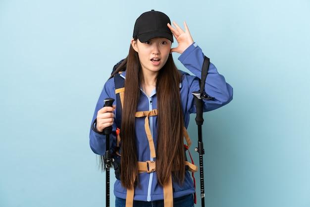 Jong chinees meisje met rugzak en trekkingstokken over blauwe muur met verrassingsuitdrukking