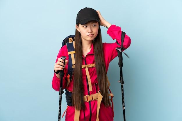 Jong chinees meisje met rugzak en trekkingstokken over geïsoleerde blauwe muur die twijfels hebben terwijl hoofd krabben