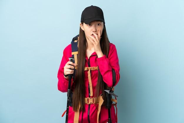 Jong chinees meisje met rugzak en trekkingstokken over geïsoleerde blauwe muur verrast en geschokt terwijl naar rechts kijkt