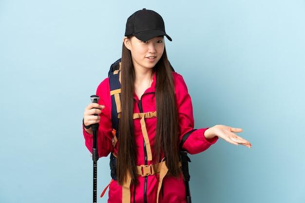 Jong chinees meisje met rugzak en wandelstokken over blauw die twijfels hebben