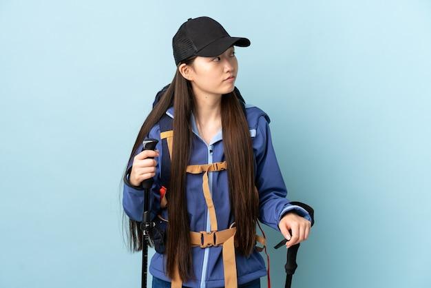 Jong chinees meisje met rugzak en wandelstokken over blauw op zoek naar de kant