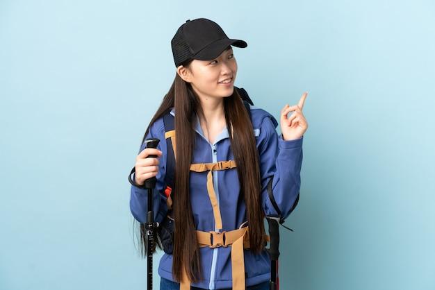 Jong chinees meisje met rugzak en wandelstokken over geïsoleerde blauwe muur die een geweldig idee benadrukt