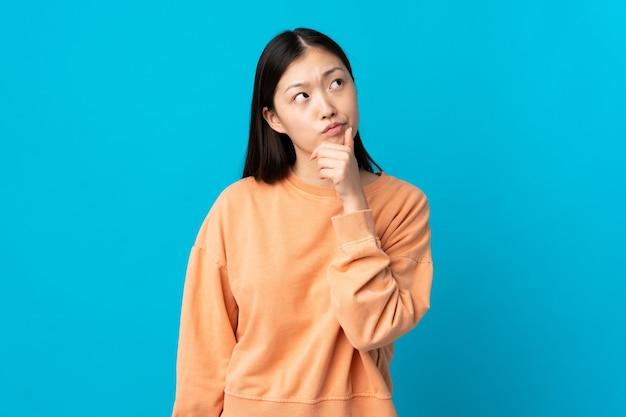 Jong chinees meisje op geïsoleerd blauw dat twijfels heeft