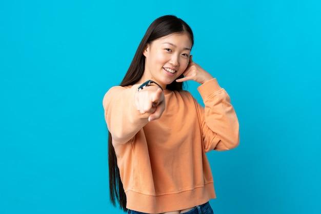 Jong chinees meisje op geïsoleerd blauw die telefoongebaar maken en voorzijde richten