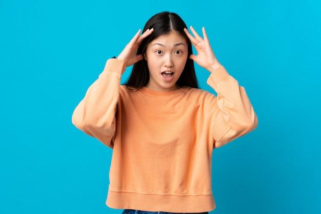 Jong chinees meisje op geïsoleerd blauw met verrassingsuitdrukking