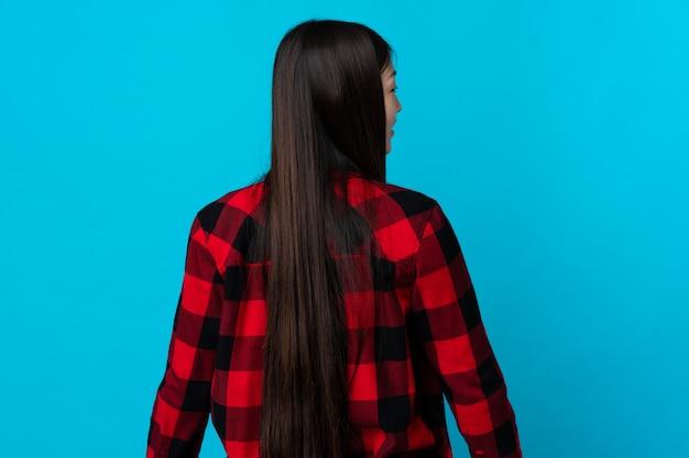 Jong chinees meisje over geïsoleerd blauw in achterpositie en kijkende kant