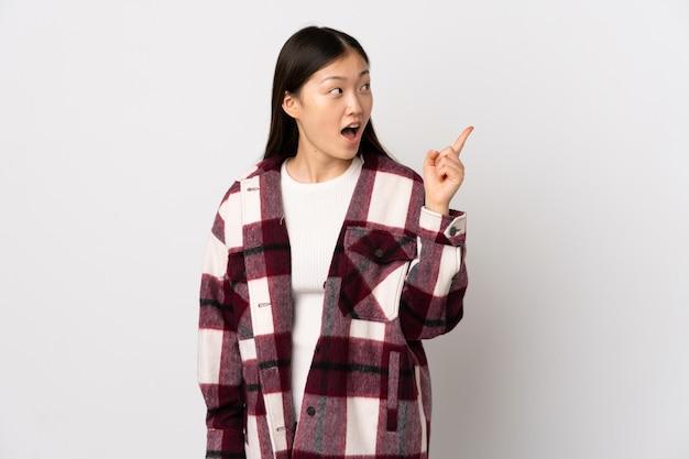 Jong chinees meisje over geïsoleerd wit die de oplossing willen realiseren terwijl het opheffen van een vinger