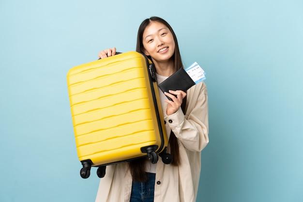 Jong chinees meisje over geïsoleerde muur in vakantie met koffer en paspoort