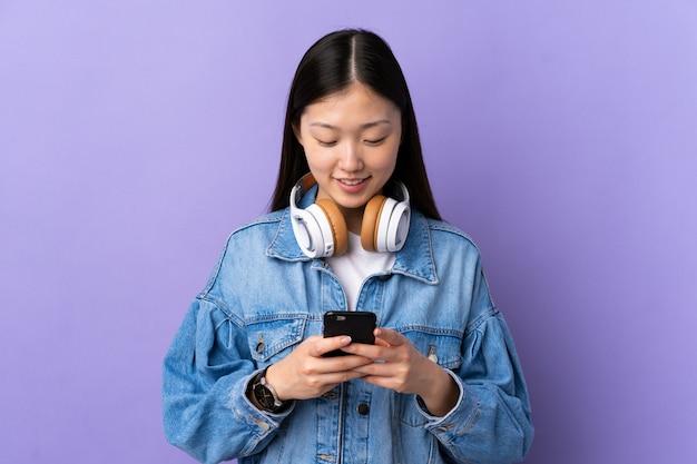 Jong chinees meisje over geïsoleerde paarse luisteren muziek en op zoek naar mobiel