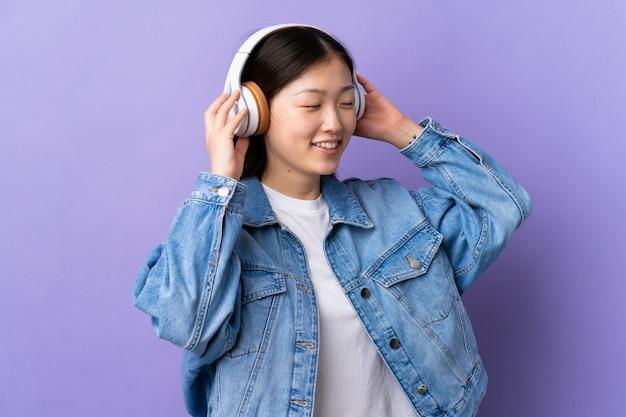 Jong chinees meisje over geïsoleerde paarse luisteren muziek en zingen