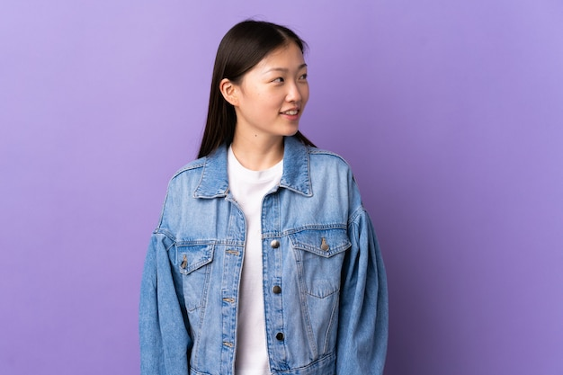 Jong chinees meisje over geïsoleerde paarse muur die naar de kant kijkt en glimlacht