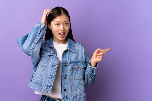 Jong chinees meisje over geïsoleerde paarse muur verrast en wijzende vinger naar de zijkant