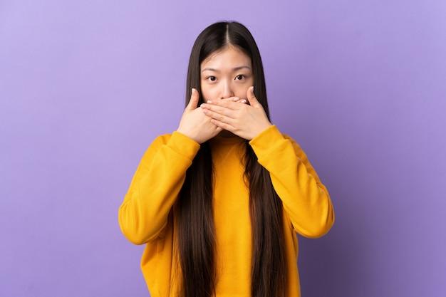 Jong chinees meisje over geïsoleerde paarse wandbekleding mond met handen