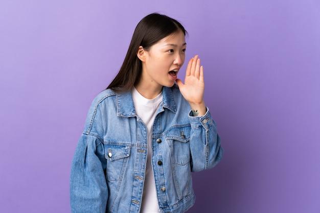 Jong chinees meisje over geïsoleerde purpere muur die met wijd open mond aan de kant schreeuwt