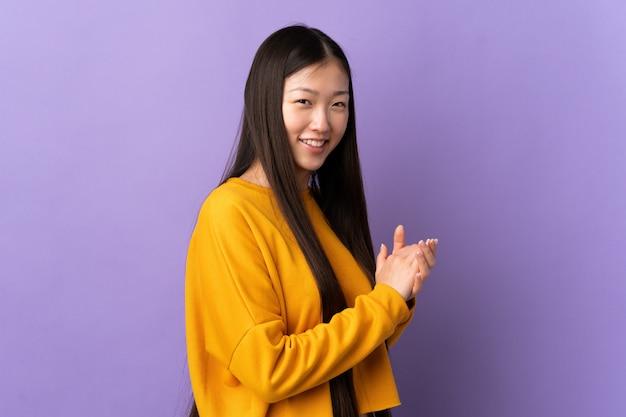 Jong chinees meisje over het geïsoleerde purpere muur toejuichen
