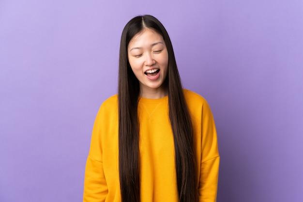 Jong chinees meisje over paars schreeuwen naar voren met wijd open mond