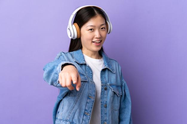 Jong chinees meisje over paarse muur luisteren muziek