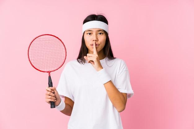 Jong chinees vrouwen speelbadminton in een roze muur die een geheim houdt of om stilte vraagt.