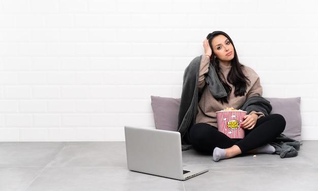 Jong colombiaans meisje dat een kom popcorns houdt en een film in laptop toont