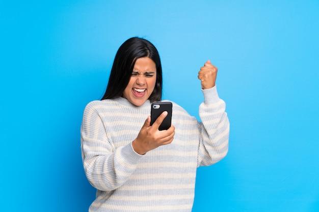Jong colombiaans meisje dat met sweater een overwinning met mobiel viert