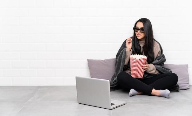 Jong colombiaans meisje in een kamer met 3d-bril en houden een grote emmer popcorns