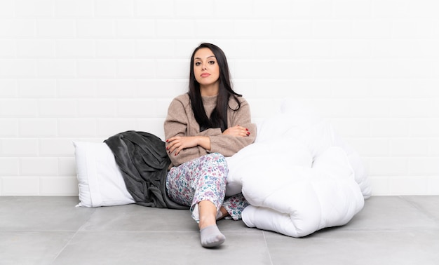 Jong colombiaans meisje in pyjama's die binnen verstoord voelen
