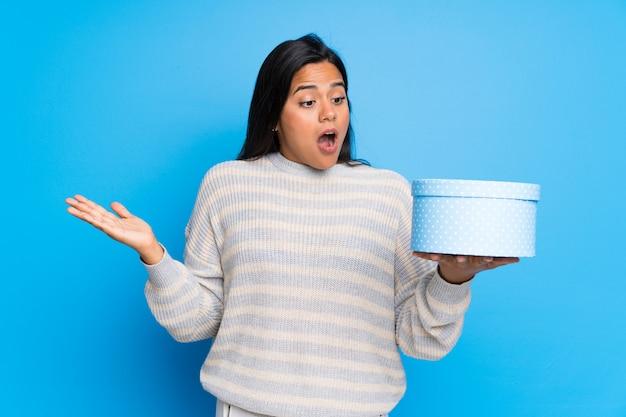 Jong colombiaans meisje met de giftdoos van de sweaterholding in handen