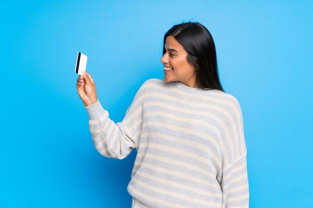Jong colombiaans meisje met sweater die een creditcard en het denken houdt