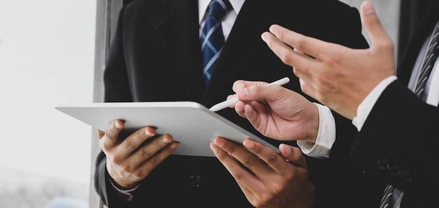Jong commercieel team dat het project samen bespreekt terwijl het gebruiken van tablet