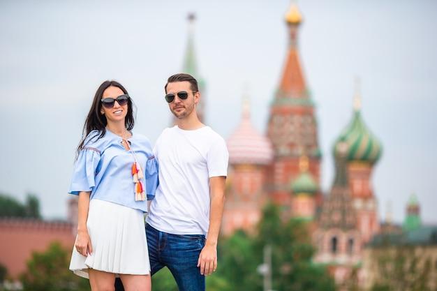 Jong daterend paar die in liefde op stadsachtergrond st basils church lopen