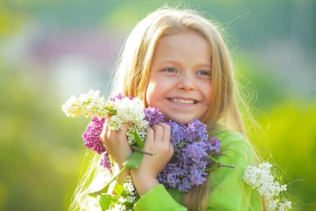 Jong de lentemeisje in de lentetuin. jonge dame voelt zich gelukkig in de natuur. gezichtsportret van grappig tienermeisje. meisje met boeket van lila.