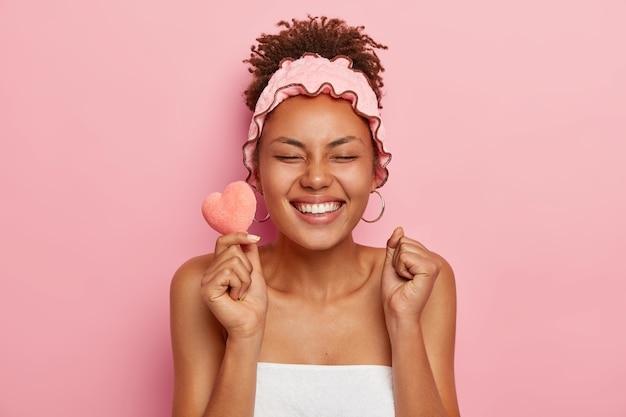 Jong dolblij vrouwelijk model met donkere huid balt vuisten van geluk, houdt kleine zachte hartvormige spons vast, sluit ogen van plezier, klaar om in bad te gaan, gewikkeld in handdoek draagt hoofdband om te douchen