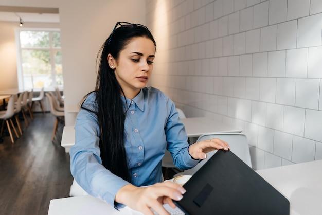 Jong donkerbruin freelancermeisje in blauw overhemd dat aan laptop werkt
