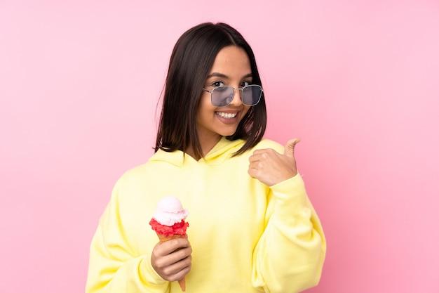 Jong donkerbruin meisje dat een cornetroomijs over geïsoleerde roze achtergrond met duimen op gebaar en het glimlachen houdt