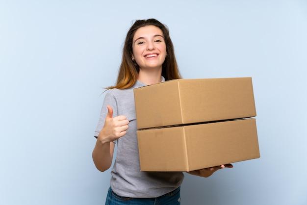 Jong donkerbruin meisje dat een doos met omhoog duim houdt